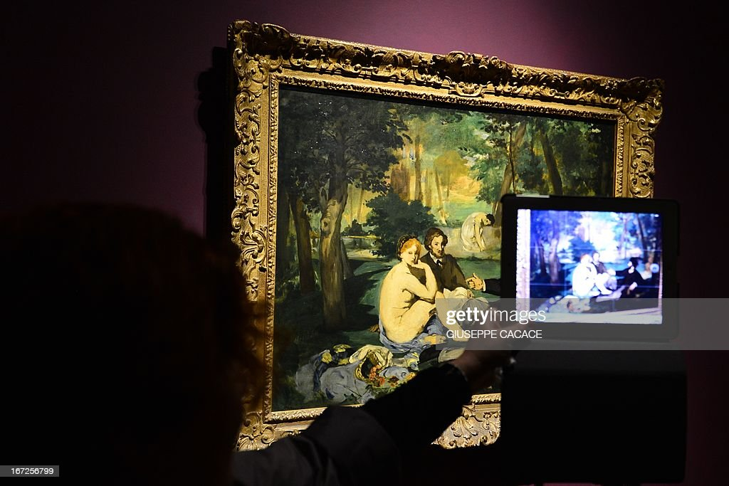 A woman takes a picture of Edouard Manet's painting named Le dejeuner sur l'herbe on April 23,2013 in Venice, during the 'Manet Return to Venice' exhibition, which runs until 18 August 2013, at the Doge's Palace in Venice. Edouard Manet's 'Olympia' will be appearing alongside the Titan's 'Venus of Urbino' a masterpice of Renaissance and source of ispiration for the French artist. AFP PHOTO / GIUSEPPE CACACE