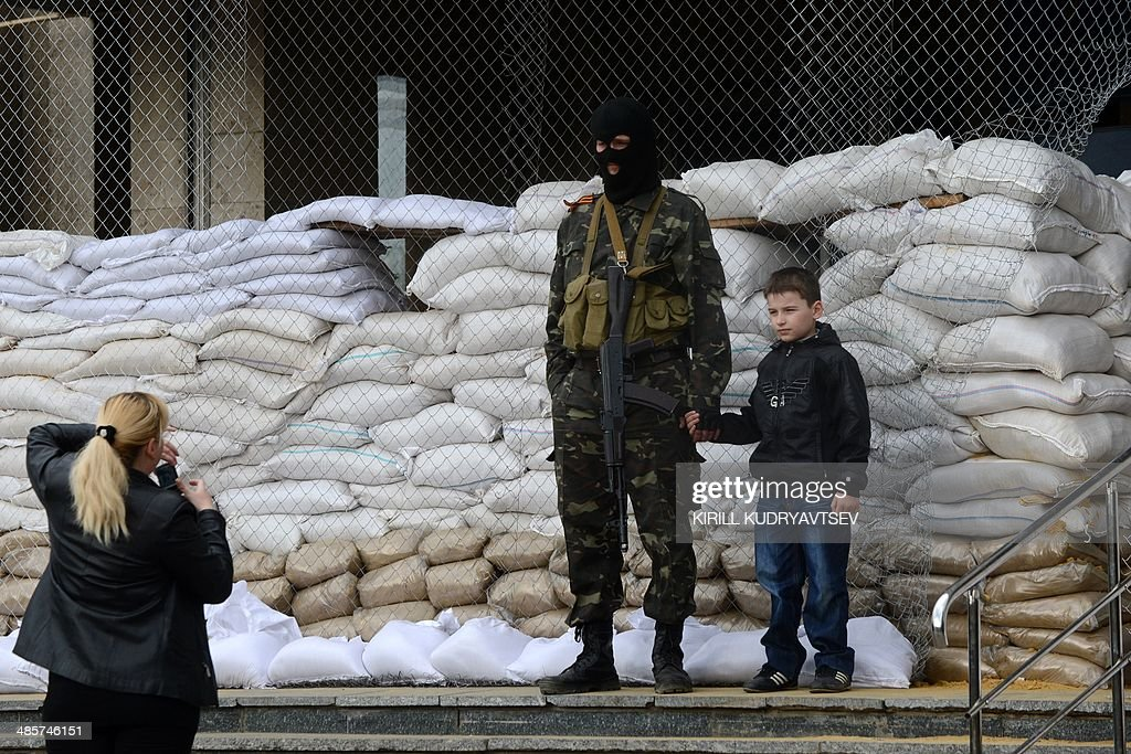 A woman takes a picture of her son standing by an armed man in military fatigue guarding a barricade outside the regional administration building in the eastern Ukrainian city of Slavyansk on April 20, 2014. Pro-Moscow rebels in Slavyansk declared a curfew there Sunday, after a gun battle with unidentified attackers killed two militants. Separatist rebels leader Vyacheslav Ponomaryov told reporters that 'the curfew comes into effect today'.