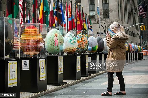 A woman takes a picture of some of the Faberge Eggs custom designed by some of the world's leading artists and designers and creativetypes that are...
