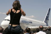 A woman takes a picture of the Airbus A380 the world's largest passenger liner during the plane's first public appearance at the 46th Paris Air Show...