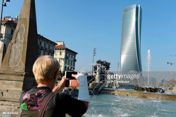 A woman takes a picture of the Generali tower also called Hadid tower designed by Zaha Hadid studio in the Citylife neighborghood western Milan on...