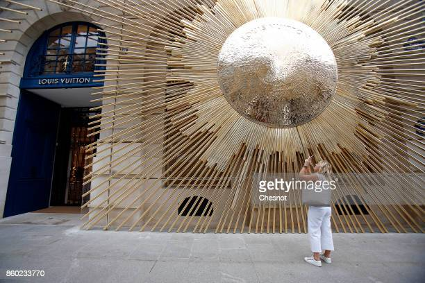 A woman takes a picture of the Louis Vuitton's New Boutique at Place Vendome on October 11 2017 in Paris France The opening of this new boutique of...
