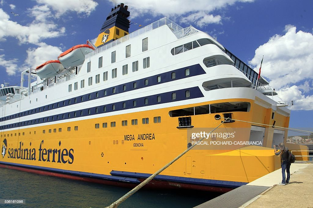 A woman takes a picture of the new ferry boat Mega Andrea of the French Corsica Ferries company, on May 31, 2016 as it is docked in the harbour of Golfo Aranci on the Italian Mediterranean island of Sardegna. The Corsica Ferries opened, on May 31, a new line between Nice, Corsica and the island of Sardegna in Italy, reinforcing its position as a leader for the maritime transport between the two neighbour islands Corsica and Sardegna. / AFP / PASCAL