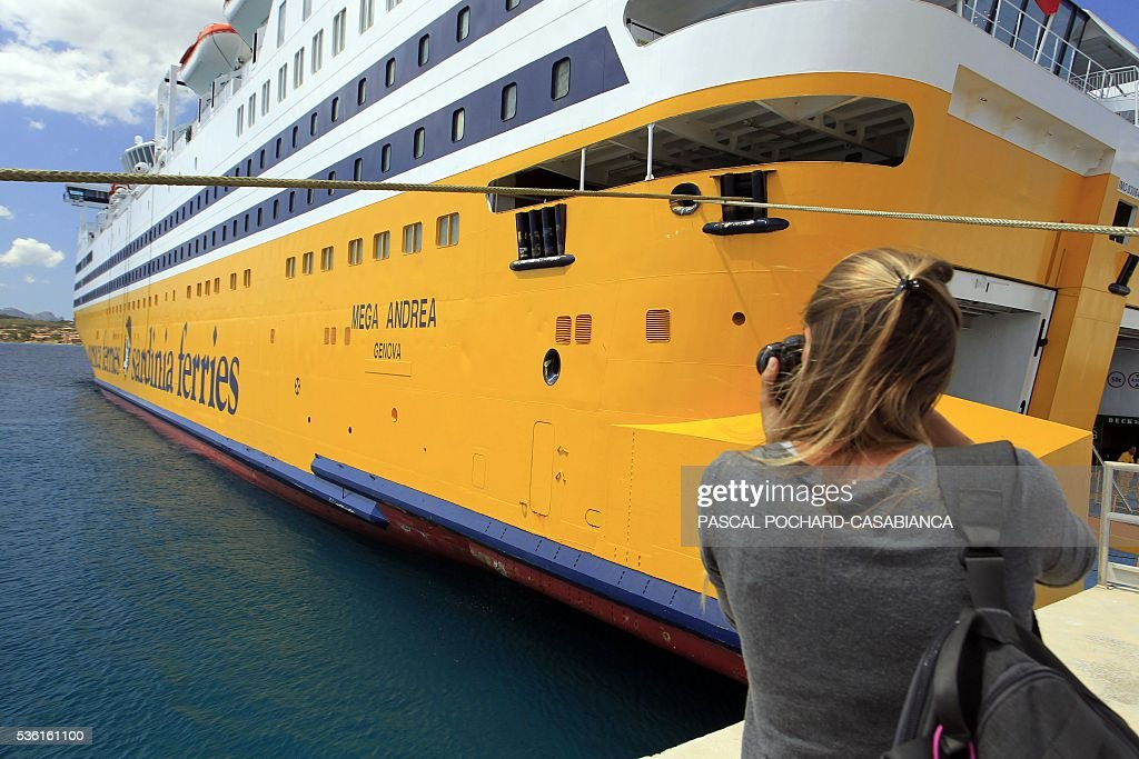 A woman takes a picture of the new ferry boat Mega Andrea of the French Corsica Ferries company, on May 31, 2016 as it is docked in the harbour of Golfo Aranci on the Italian Mediterranean island of Sardegna. The Corsica Ferries opened, on May 31, a new line between Nice, Corsica and the island of Sardegna in Italy, reinforcing its position as a leader for the maritime transport between the two neighbour islands Corsica and Sardegna. / AFP / Pascal POCHARD