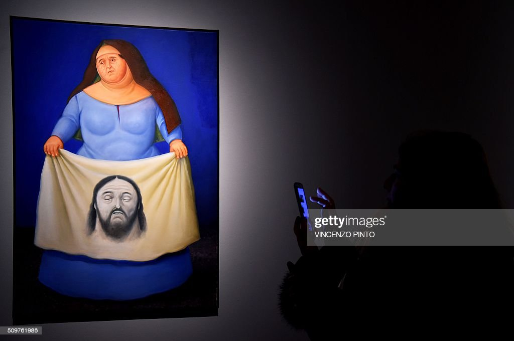 A woman takes a picture of the painting 'Veronica' by Colombian artist Fernando Botero on February 12, 2016 during the 'Via Crucis' exhibition at the Palazzo delle Esposizioni in Rome. The exhibition runs until May 1, 2016 / AFP / Vincenzo PINTO / RESTRICTED TO EDITORIAL USE - MANDATORY MENTION OF THE ARTIST UPON PUBLICATION - TO ILLUSTRATE THE EVENT AS SPECIFIED IN THE CAPTION