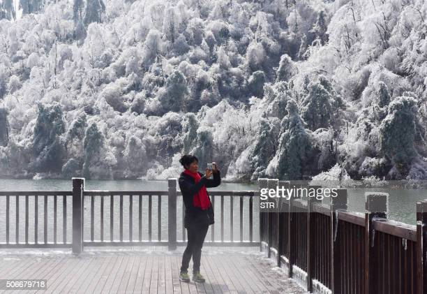 A woman takes a picture of the snow and ice in Hangzhou in eastern China's Zhejiang province on January 25 2016 Snow sleet and icy winds across Asia...