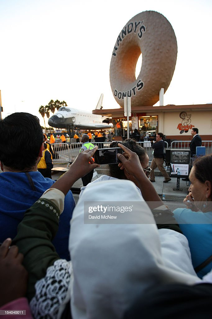 A woman takes a picture of the space shuttle Endeavour as it's transported to the California Science Center in Exposition Park from Los Angeles International Airport (LAX) on October 12, 2012 in Los Angeles, California. Endeavour was flown cross-country atop NASA's Shuttle Carrier Aircraft from Kennedy Space Center in Florida to LAX on its last flight ever on September 21. From there, it was transported to the California Science Center in Exposition Park where it will be on permanent public display. Completed in 1991, Endeavour was built to replace the space shuttle Challenger which disintegrated during a catastrophic re-entry accident. This fifth and final space shuttle orbiter circled the earth 4,671 times and traveled nearly 123 million miles during its 25 missions from 1992 to 2011.