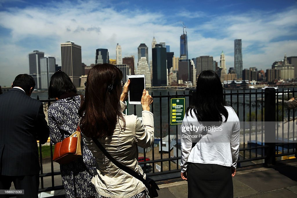 A woman takes a picture with a tablet of the Manhattan skyline with One World Trade Center, now the tallest building in the United States on May 10, 2013 in New York City. After more than 11 years of construction and planning, One World Trade Center reached its final height Friday morning of 1,776 feet. When it opens for business in 2014, One World Trade center will be home to companies including Conde Nast and Vantone Holdings China Center. One World Trade Center is built on the site where the September 11, 2001 attacks toppled the original World Trade Center towers.