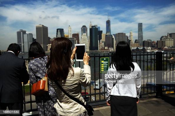 A woman takes a picture with a tablet of the Manhattan skyline with One World Trade Center now the tallest building in the United States on May 10...