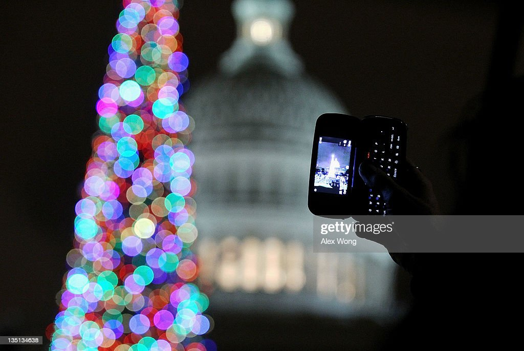 A woman takes a picture with her cellular phone after U.S. Speaker of the House Rep. John Boehner (R-OH) lights up the 2011 Capitol Christmas Tree with Seven-year-old Johnny Crawford of Sonora, California, at the West Front of the Capitol December 6, 2011 on Capitol Hill in Washington, DC. This year's tree was a 65-foot tall Sierra white fir from the Stanislaus National Forest in California.