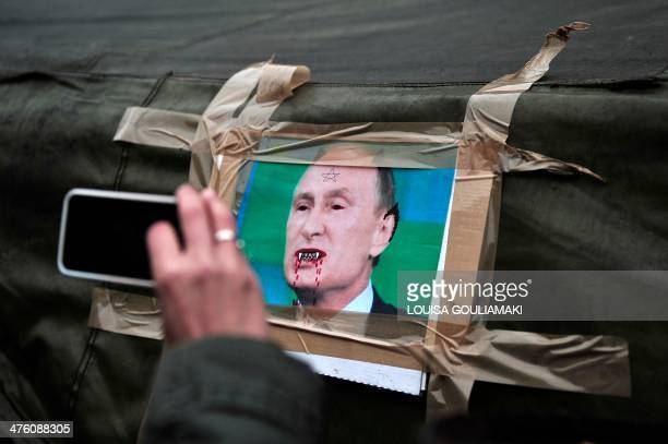 A woman takes a picture with her mobile phone of a caricature of Russian President Vladimir Putin stuck onto a tent within a rally to protest...