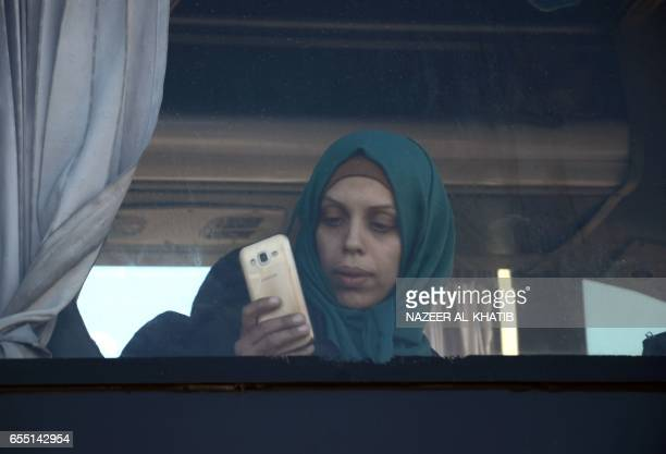 A woman takes a picture with her phone as Syrians who were evacuated from Waer the last oppositionheld district of Homs arrive in the northern Syrian...