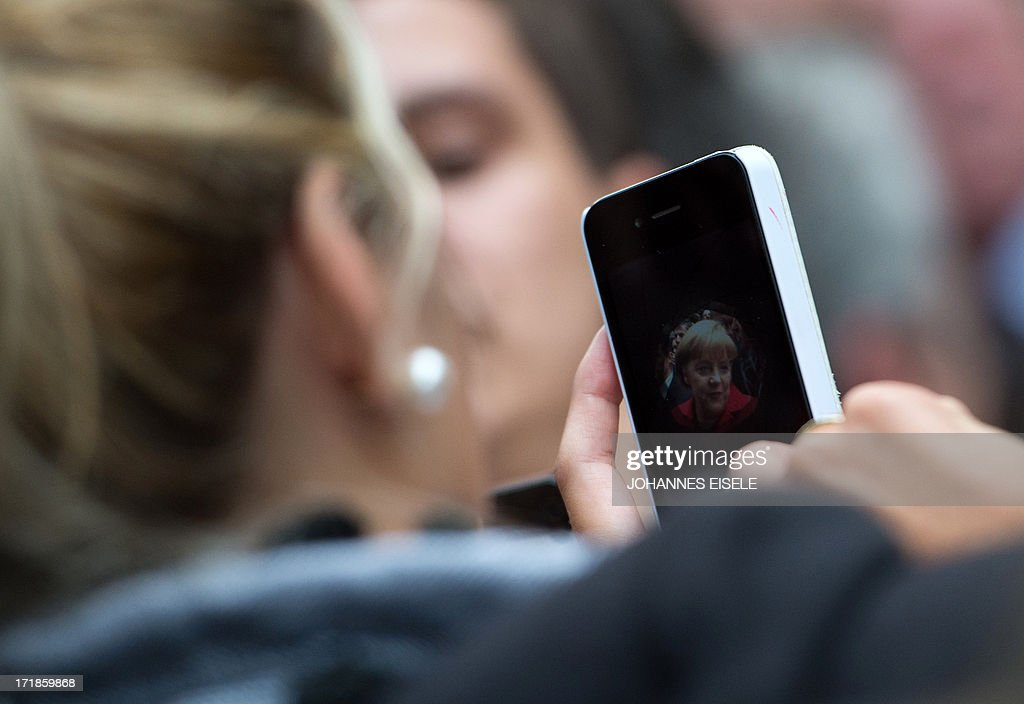A woman takes a picture with her smartphone of German chancellor Angela Merkel as she attends an open house event in the Garden of the former west-German chancellory Palais Schaumburg in Bonn, western Germany on June 29, 2013. AFP PHOTO / JOHANNES EISELE
