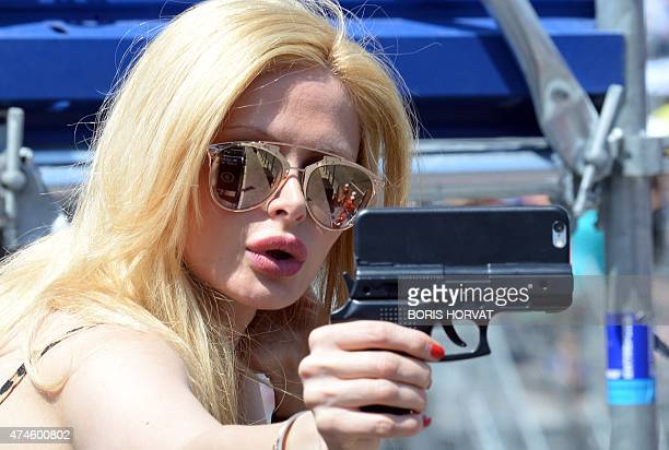 A woman takes a selfie as she attends the Monaco Formula One Grand Prix at the Monaco street circuit in MonteCarlo on May 24 2015 AFP PHOTO / BORIS...