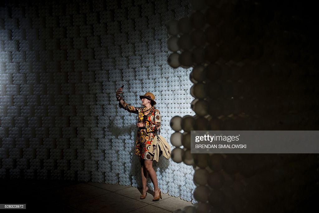 A woman takes a selfie in front of a wall at the for Creative selfie wall