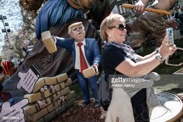 A woman takes a selfie in front of the wooden structures made by carpenters and artists during Las Fallas festival in Valencia Spain on March 19 2017
