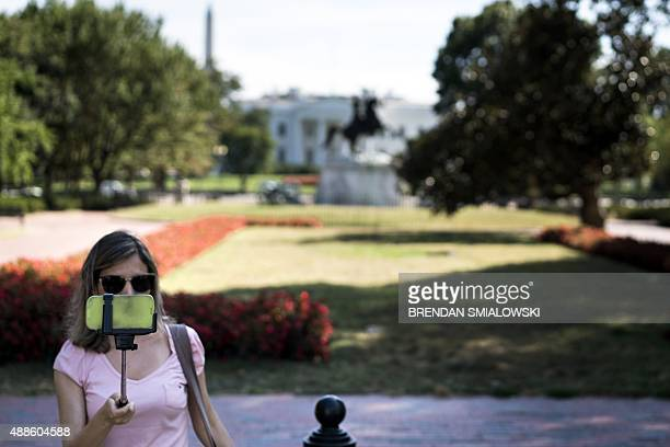 A woman takes a selfie in Lafayette Park in front of the White House September 16 2015 in Washington DC AFP PHOTO/BRENDAN SMIALOWSKI