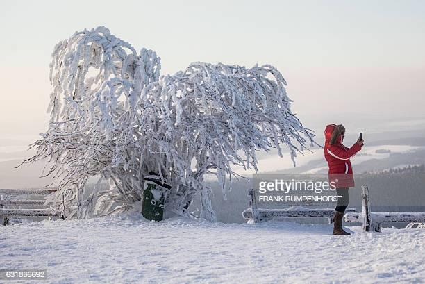 A woman takes a selfie in the frosted winter landscape on the Großer Feldberg in the mountainous Taunus area near Schmitten central Germany on...