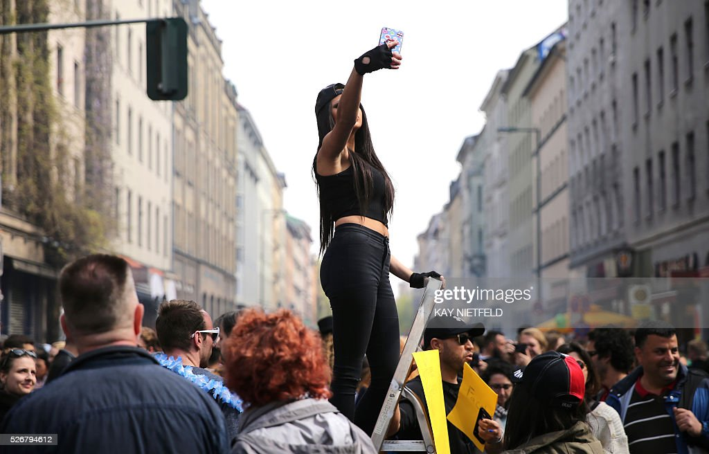 A woman takes a 'selfie' on a 'selfie ladder' at the 'Myfest' in Berlin, on May 1, 2016. / AFP / dpa / Kay Nietfeld / Germany OUT