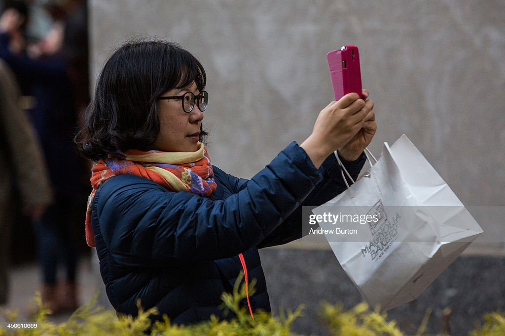 A woman takes a 'selfie' outside Rockefeller Center on November 19, 2013 in New York City. Oxford Dictionary named 'Selfie' the new word of the year. The word is defined as 'a photograph that one has taken of oneself, typically with a smartphone or webcam and uploaded to a social media website.' The terms 'binge-watch' and 'twerk' were shortlisted.