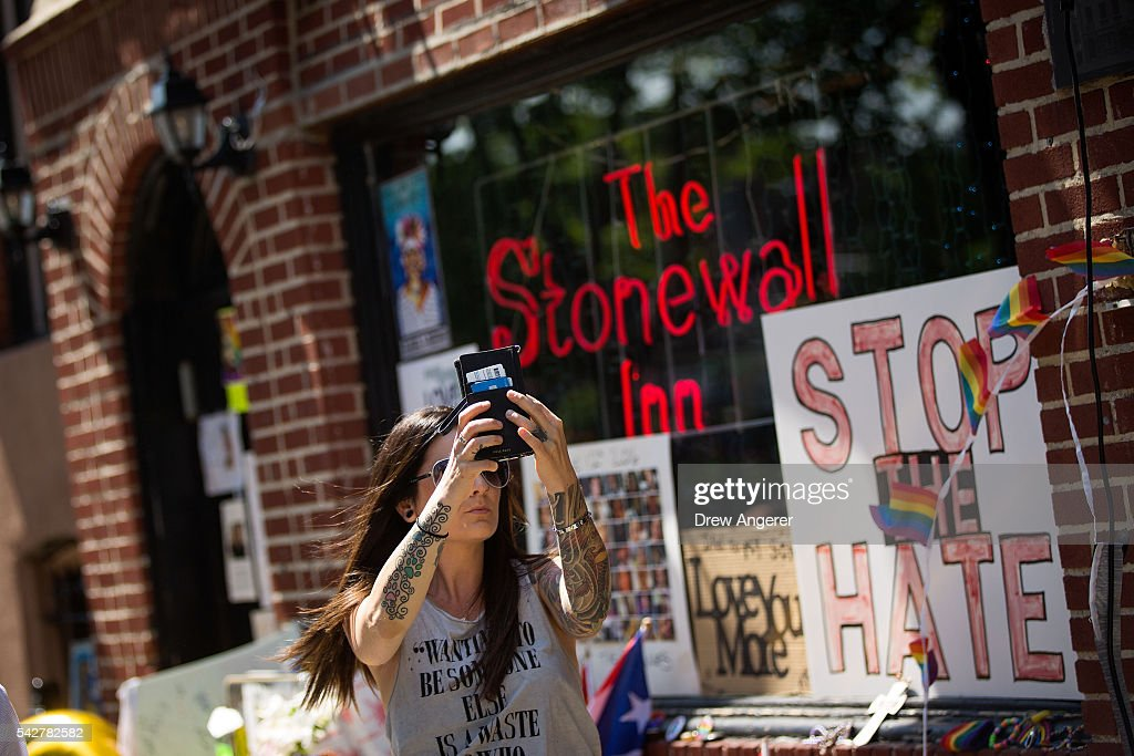A woman takes a 'selfie' photograph in front of the Stonewall Inn on June 24, 2016 in New York City. President Barack Obama designated Stonewall Inn and approximately 7.7 acres surrounding it as the first national monument dedicated 'to tell the story of the struggle for LGBT rights.' The tavern is considered the birthplace of the modern gay rights movement, where patrons fought back against police persecution in 1969.