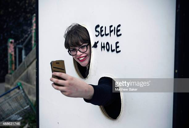 A woman takes a selfie through the 'Selfie Hole' at Banksy's Dismaland on September 10 2015 in WestonSuperMare England