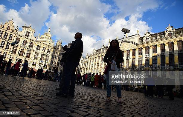 A woman takes a selfie using a selfie stick on Brussel's Grand Place on April 30 2015 AFP PHOTO / EMMANUEL DUNAND