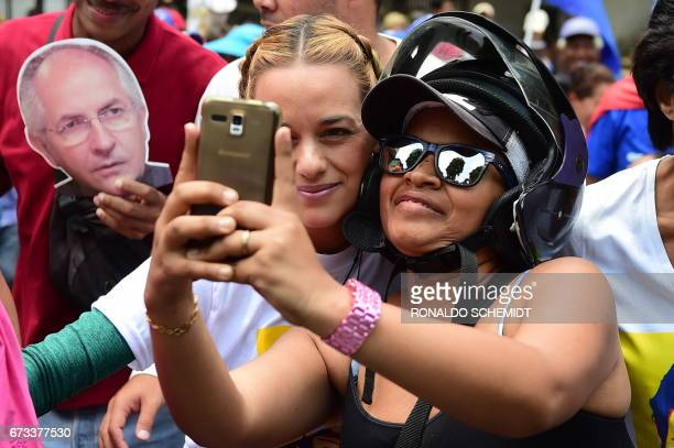 A woman takes a selfie with opposition leader and wife of jailed opposition leader Leopoldo Lopez Lilian Tintori during a protest march in Caracas on...