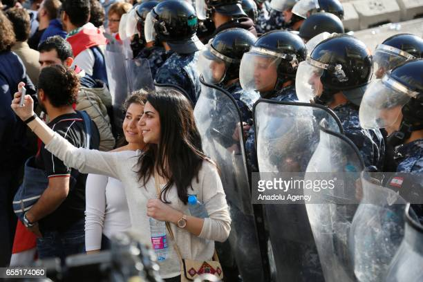 A woman takes a selfie with security forces as Lebanese people gather at Riad Al Solh Square to protest the corruption and the government's new tax...