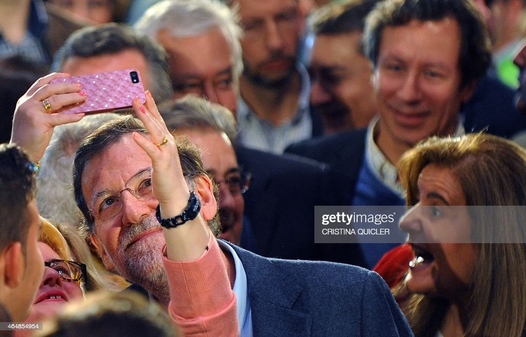 A woman takes a selfie-photo with Spanish Prime Minister and leader of ruling Popular Party (PP) Mariano Rajoy (L) next to Spanish Minister of Employment and Social Security <a gi-track='captionPersonalityLinkClicked' href=/galleries/search?phrase=Fatima+Banez&family=editorial&specificpeople=8764943 ng-click='$event.stopPropagation()'>Fatima Banez</a> (R) during a political meeting to present the 109 PP candidates for the Parliament of Andalucia election on March 1, 2015. Rajoy today called on his Greek counterpart to be 'serious' about his country's debt-wracked economy after Alexis Tsipras accused other eurozone stragglers of trying to undermine negotiations with Brussels for a bailout extension.