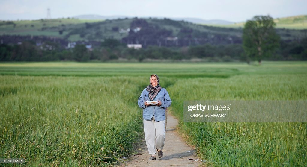A woman takes a walk across a field next to a makeshift camp for migrants and refugees near the village of Idomeni not far from the Greek-Macedonian border on April 30, 2016. Some 54,000 people, many of them fleeing the war in Syria, have been stranded on Greek territory since the closure of the migrant route through the Balkans in February. / AFP / TOBIAS