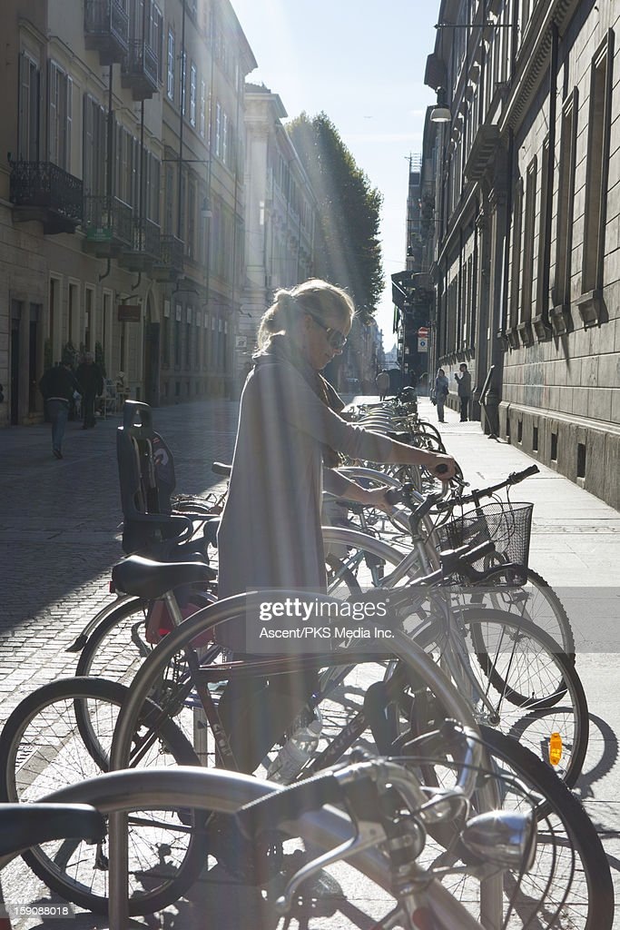 Woman takes biker from bike share stand, street : Stock Photo