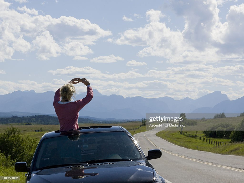 Woman takes cell phone picture from car's sunroof : Stock Photo
