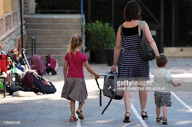 A woman takes children at the Abbe de l'Epee elementary school on September 3 2013 in Marseille southern France prior to enter her classroom on the...