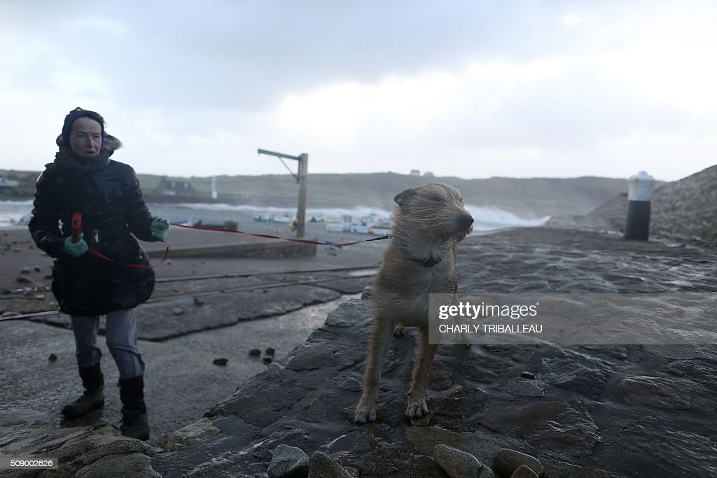 A woman takes her dog for a walk at the harbour in Auderville, northwestern France, on February 8, 2016, as strong winds hit the region. Winds of over 130 kh/h were recorded in the region where 16 departments have been placed under alert for wind and flooding waves. / AFP / CHARLY TRIBALLEAU