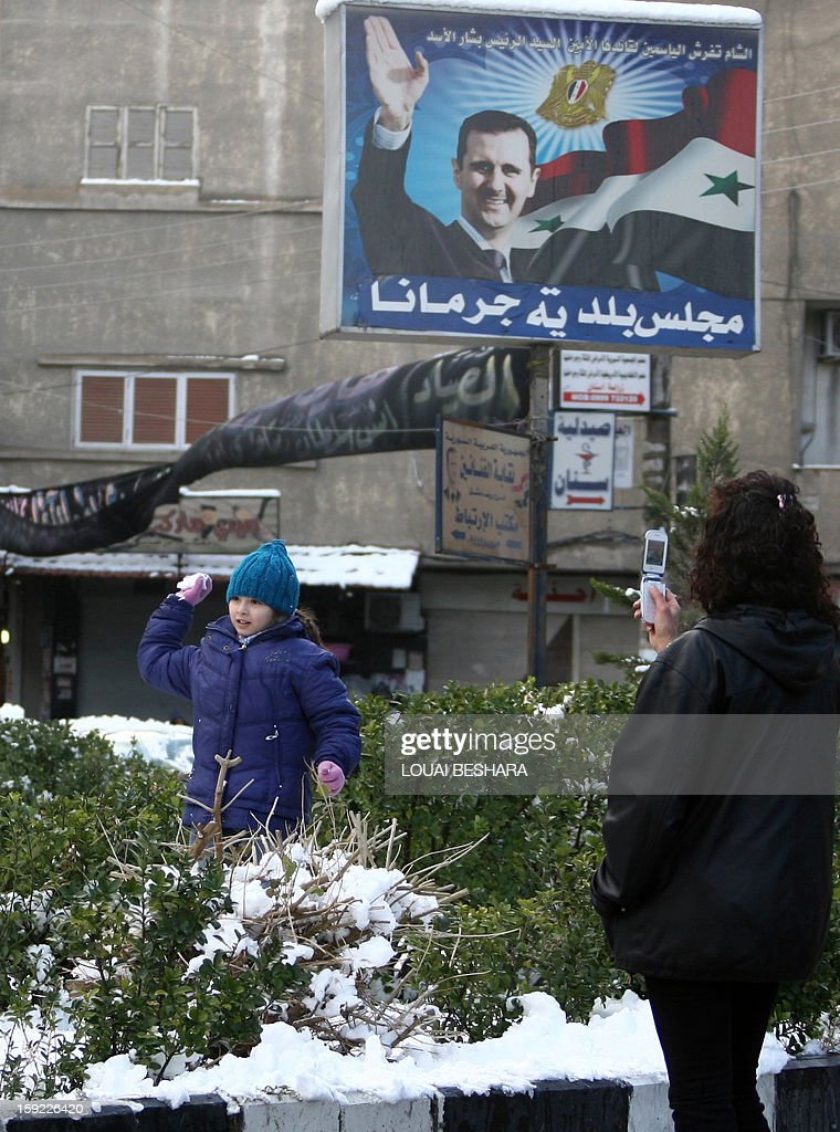 A woman takes in picture her kid playing with snow balls in front of a giant poster featuring Syria's president Bachar al-Assad on January 10, 2013 in the Syrian capital of Damascus. Snow carpeted Syria's war-torn cities but sparked no let-up in the fighting, instead heaping fresh misery on a civilian population already enduring a chronic shortage of heating fuel and daily power cuts.