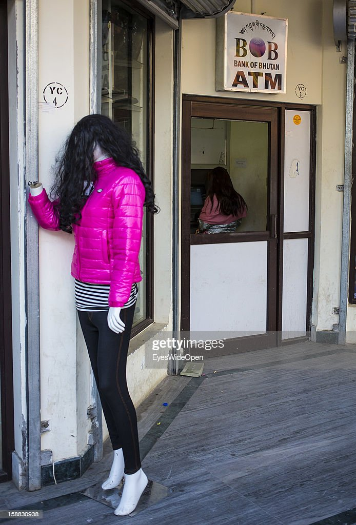 A woman takes money at an ATM cash machine of the Bank of Bhutan on November 18, 2012 in Thimbu, Bhutan.