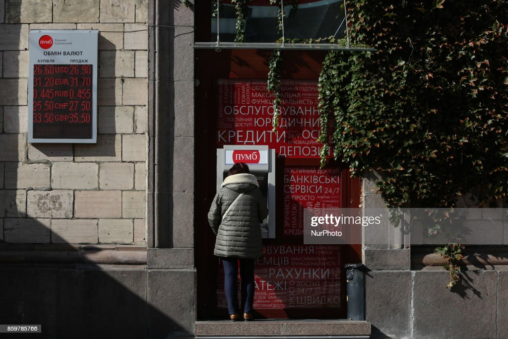 A woman takes money from a bank machine point at Khreshchatyk street in Kyiv, October 10, 2017.