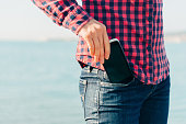 Woman takes out mobile phone of her pocket of jeans on beach near the sea to make self-portrait or to photograph the sea