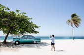 Woman takes photo of American car on the beach.