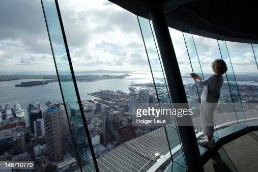 Woman takes photograph from atop Auckland Sky Tower.
