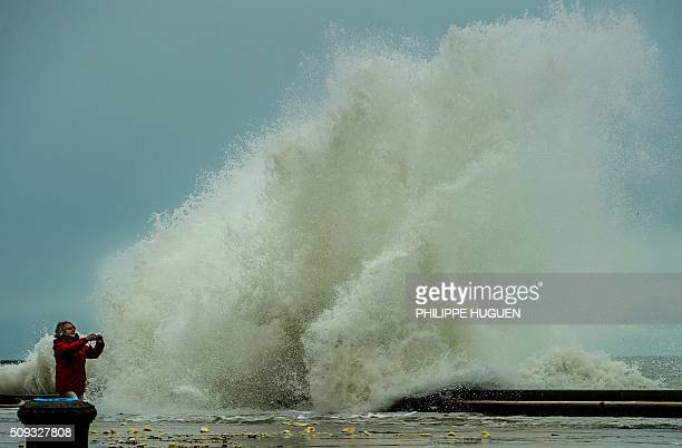 A woman takes photographs as w aves break against the Wimereux breakwaterin Wimereux northern France on February 9 2016 High winds buffeted...