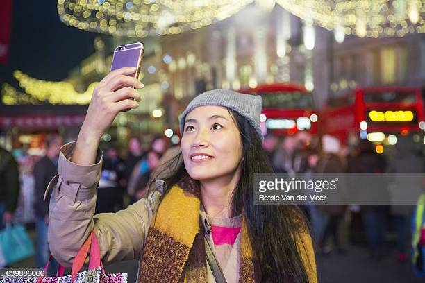 Woman takes photographs of christmas decorations in urban street.