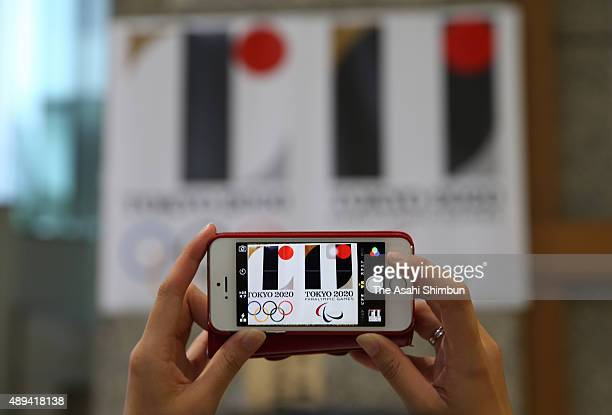 A woman takes photographs of the 2020 Tokyo Olympic and Paralympic Games Emblems before being removed at Tokyo Metropolitan headquarters on September...