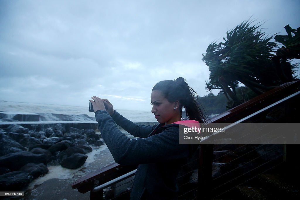 A woman takes photographs of wild conditions at Snapper Rocks as Queensland experiences severe rains and flooding from Tropical Cyclone Oswald on January 28, 2013 in Gold Coast, Australia. Hundreds have been evacuated from the towns of Gladstone and Bunderberg while the rest of Queensland braces for more flooding.