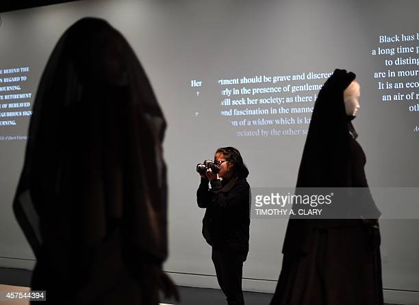 A woman takes photos during a press preview October 20 2014 as the Metropolitan Museums Costume Institute opens Death Becomes Her A Century of...