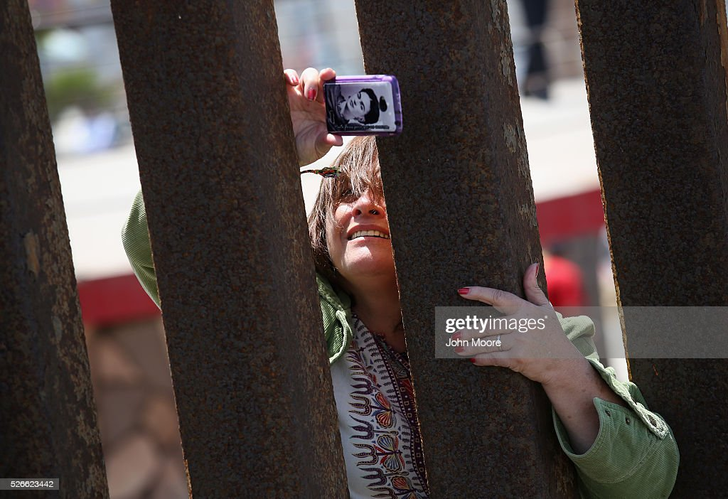 A woman takes photos from the Mexican side into the United States at the U.S.-Mexico Border fence during a 'Opening the Door of Hope' event on April 30, 2016 in San Diego, California. Five families, with some members living in Mexico and others in the United States, were permitted to meet and embrace for three minutes each at a door in the fence, which the U.S. Border Patrol opened to celebrate Mexican Children's Day. It was only the third time the fence, which separates San Diego from Tijuana, had been opened for families to briefly reunite. The event was planned by the immigrant advocacy group Border Angels.