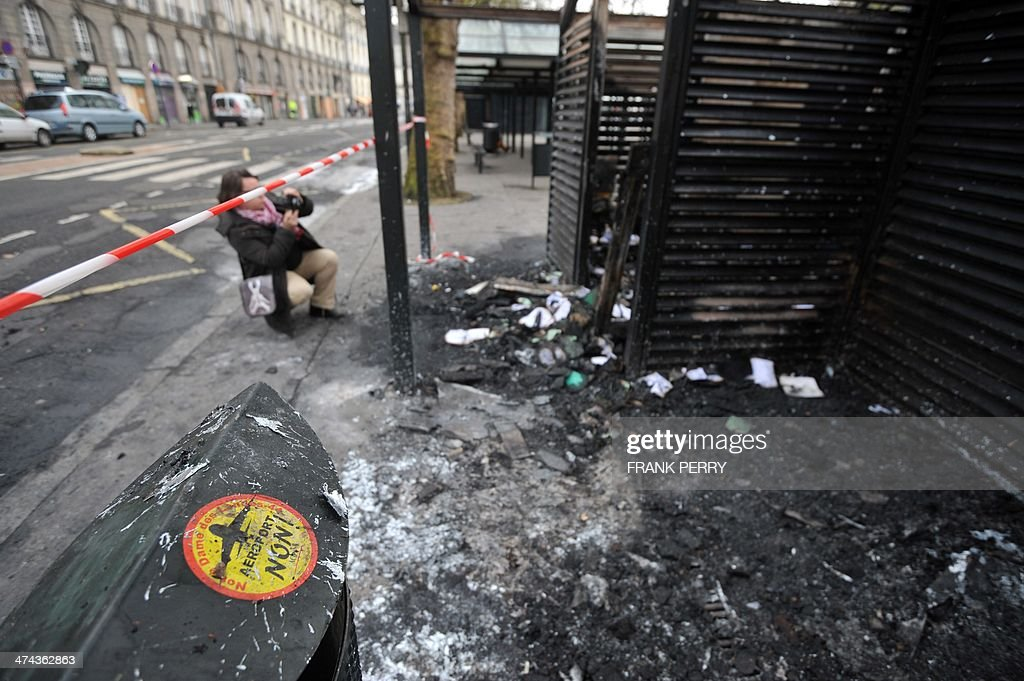 A woman takes photos of a tramway station in Nantes, western France, on February 23, 2014 which was burnt down by protesters opposed to plans to build the Notre-Dames-des-Landes airport for the French city of Nantes. Protesters smashed shop windows on February 22 and hurled paving stones at police, who answered with tear gas and rubber bullets. Tens of thousands of protesters against building the airport on protected swampland swarmed the western city's Petite Hollande square, the latest in a string of demonstrations against the pet project of Prime Minister Jean-Marc Ayrault.