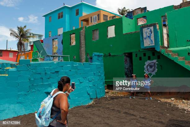 A woman takes photos of her two daughters in the neighbourhood of La Perla where the video 'Despacito' was recorded in San Juan on July 22 2017...