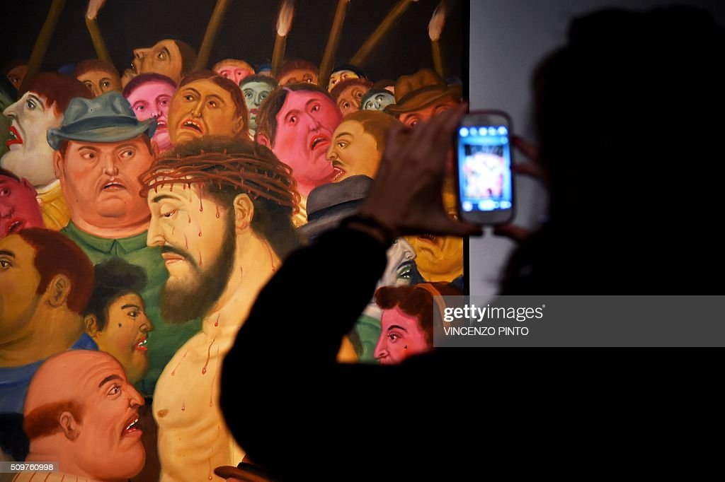 A woman takes photos of the painting 'Jesus and the crowd' by Colombian artist Fernando Botero on February 12, 2016 during the 'Via Crucis' exhibition at Rome's Palazzo delle Esposizioni. The exhibition runs until May 1, 2016. / AFP / Vincenzo PINTO